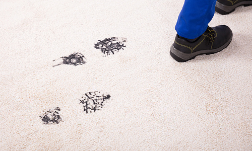 Man leaving black footprints on white carpet